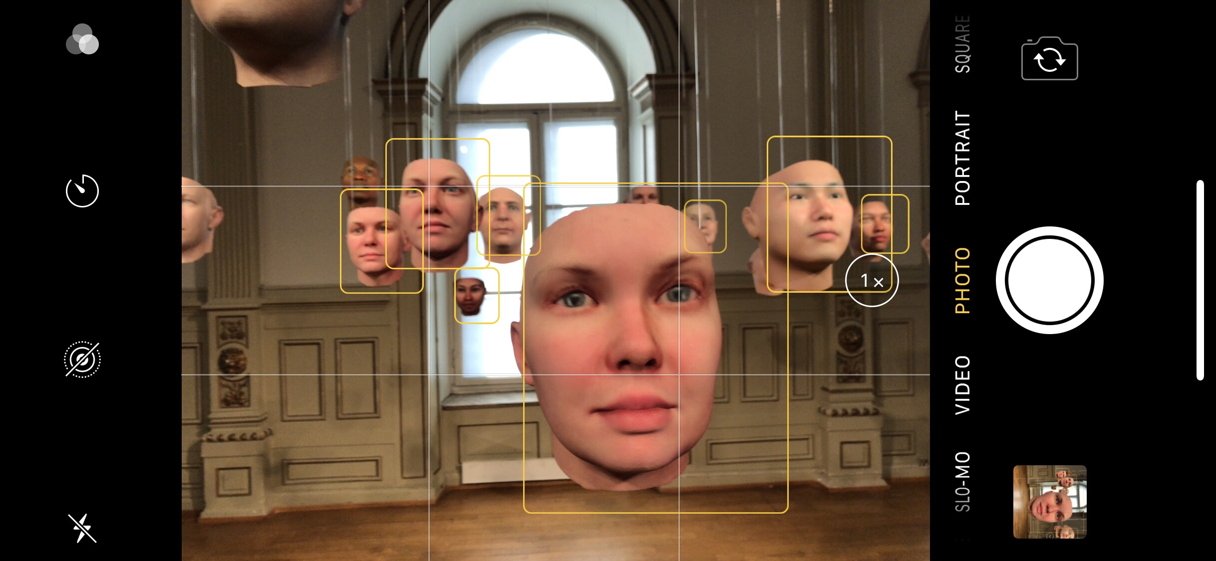 A screenshot of the iPhone camera interface showing hanging masks resembling human faces in an art gallery, and yellow squares around each mask indicating that the phone camera has recognised a human face.